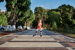 Beautiful little happy girl rollerblading through the city-park path in the warm sunshiny summer day. Cute sportive girl dressed in the sportwear. Beautiful Stock Photography