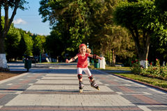 Beautiful little happy girl rollerblading through the city-park path in the warm sunshiny summer day. Cute sportive girl dressed in the sportwear. Beautiful Stock Images