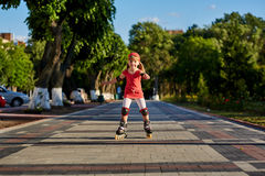 Beautiful little happy girl rollerblading through the city-park path in the warm sunshiny summer day. Cute sportive girl dressed in the sportwear. Beautiful Royalty Free Stock Images