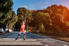 Beautiful little happy girl rollerblading through the city-park path in the warm sunshiny summer day. Cute sportive girl dressed in the sportwear. Beautiful Royalty Free Stock Photos