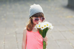 Beautiful little hipster girl with flowers. Photo of beautiful little hipster girl with flowers Stock Image