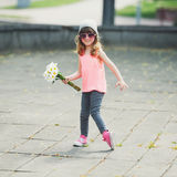Beautiful little hipster girl with flowers. Photo of beautiful little hipster girl with flowers Stock Photography