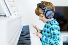 Beautiful little kid boy playing piano in living room or music school. Beautiful little kid boy with headphones playing piano in living room or music school Royalty Free Stock Photo