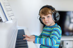Beautiful little kid boy playing piano in living room or music school stock photography
