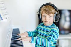 Beautiful little kid boy playing piano in living room or music school. Beautiful little kid boy with headphones playing piano in living room or music school Stock Image