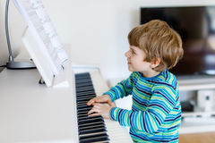Beautiful little kid boy playing piano in living room or music school. Preschool child having fun with learning to play music instrument. Education, skills Stock Images