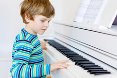 Beautiful little kid boy playing piano in living room or music school. Preschool child having fun with learning to play music instrument. Education, skills Stock Photos