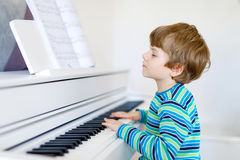Beautiful little kid boy playing piano in living room or music school. Preschool child having fun with learning to play music instrument. Education, skills Stock Photo