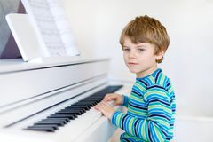 Beautiful little kid boy playing piano in living room or music school. Preschool child having fun with learning to play music instrument. Education, skills Stock Image
