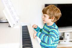 Beautiful little kid boy playing piano in living room or music school. Preschool child having fun with learning to play music instrument. Education, skills Royalty Free Stock Image