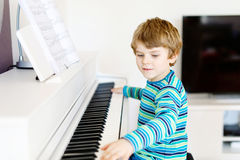 Beautiful little kid boy playing piano in living room or music school. Preschool child having fun with learning to play music instrument. Education, skills Royalty Free Stock Photos