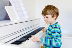 Beautiful little kid boy playing piano in living room or music school. Preschool child having fun with learning to play music instrument. Education, skills Royalty Free Stock Photo