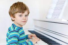 Beautiful little kid boy playing piano in living room or music school. Preschool child having fun with learning to play music instrument. Education, skills Stock Photography