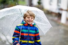 Beautiful little kid boy on way to school walking during sleet, rain and snow with an umbrella on cold day. Happy and. Joyful child in colorful fashion casual stock photography