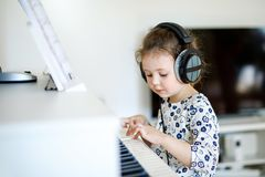 Beautiful little kid girl playing piano in living room or music school. Preschool child having fun with learning to play. Beautiful little kid girl playing piano royalty free stock photography