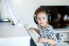 Beautiful little kid girl playing piano in living room or music school. Beautiful little kid girl playing piano with headphones in living room or music school Royalty Free Stock Photography