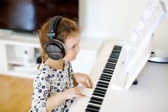 Beautiful little kid girl playing piano in living room or music school. Beautiful little kid girl playing piano with headphones in living room or music school Stock Photo