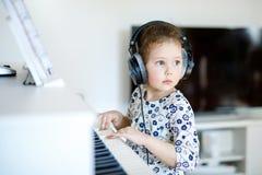 Beautiful little kid girl playing piano in living room or music school. Beautiful little kid girl playing piano with headphones in living room or music school Stock Photos