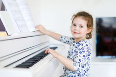 Beautiful little kid girl playing piano in living room or music school. Preschool child having fun with learning to play music instrument. Education, skills royalty free stock photo