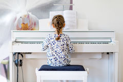 Beautiful little kid girl playing piano in living room or music school. Preschool child having fun with learning to play music instrument. Education, skills Royalty Free Stock Images