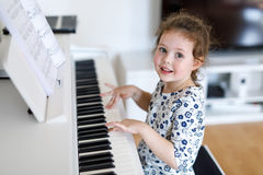 Beautiful little kid girl playing piano in living room or music school Royalty Free Stock Photo