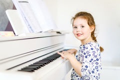 Beautiful little kid girl playing piano in living room or music school. Preschool child having fun with learning to play music instrument. Education, skills Stock Photography