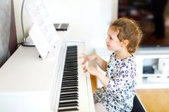 Beautiful little kid girl playing piano in living room or music school. Preschool child having fun with learning to play. Music instrument. Education, skills royalty free stock image