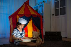Beautiful little kid sailor looking history book. Beautiful pretty little kid sailor looking history book pointing information for teddy bear toy and explaining Royalty Free Stock Photo