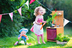Beautiful little kids playing with toy kitchen in the garden Stock Photo