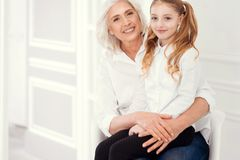 Beautiful little lady sitting on lap of her cheerful grandmother royalty free stock photos