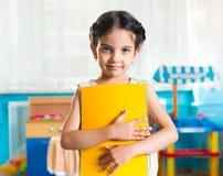 Beautiful little latin girl portrait in daycare. Beautiful little latin girl portrait with book in daycare stock photo