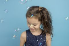 Beautiful little long hair girl playing with bubbles at a kinder playground. With blue background royalty free stock images