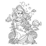 Beautiful little mermaid girl sits on a rock and combs her hair Royalty Free Stock Photos