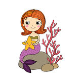 Beautiful little mermaid with a starfish sitting on a stone. Stock Image