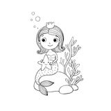Beautiful little mermaid with a starfish sitting on a stone. Royalty Free Stock Image