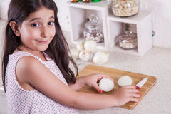 Beautiful little middle eastern 7 years old girl is working with knife and onion in the white kitchen. studio shot. Stock Image