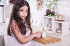 Beautiful little middle eastern 7 years old girl is working with knife and onion in the white kitchen. studio shot. Royalty Free Stock Photo