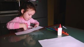 Beautiful little preschool European girl in pink sweater sitting by the table at home alone cutting shapes from paper. stock footage