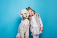 Beautiful little princess with dog. Friendship. Pets. Studio portrait over blue background Stock Photography