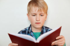 Beautiful little pupil with blond hair looking seriously into the book having concentrated expression while getting ready with hom. Ework. Education, childhood Stock Photos