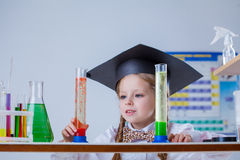 Beautiful little pupil posing with test tubes Royalty Free Stock Photo