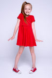 Beautiful little redhead girl in red dress and sneakers posing like model on white background. Stock Image