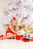 Beautiful little Santa girl near the Christmas tree.  Happy girl Royalty Free Stock Images