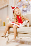 Beautiful little Santa girl near the Christmas tree.  Happy girl Royalty Free Stock Photography