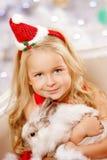 Beautiful little Santa girl near the Christmas tree.  Happy girl Stock Photo