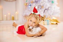 Beautiful little Santa girl near the Christmas tree.  Happy girl Royalty Free Stock Photos