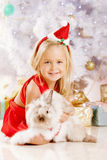 Beautiful little Santa girl near the Christmas tree.  Happy girl Royalty Free Stock Photos