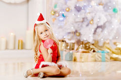 Beautiful little Santa girl near the Christmas tree.  Happy girl Stock Images
