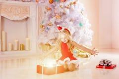 Beautiful little Santa girl near the Christmas tree.  Happy girl Stock Photos