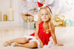 Beautiful little Santa girl near the Christmas tree.  Happy girl Stock Image
